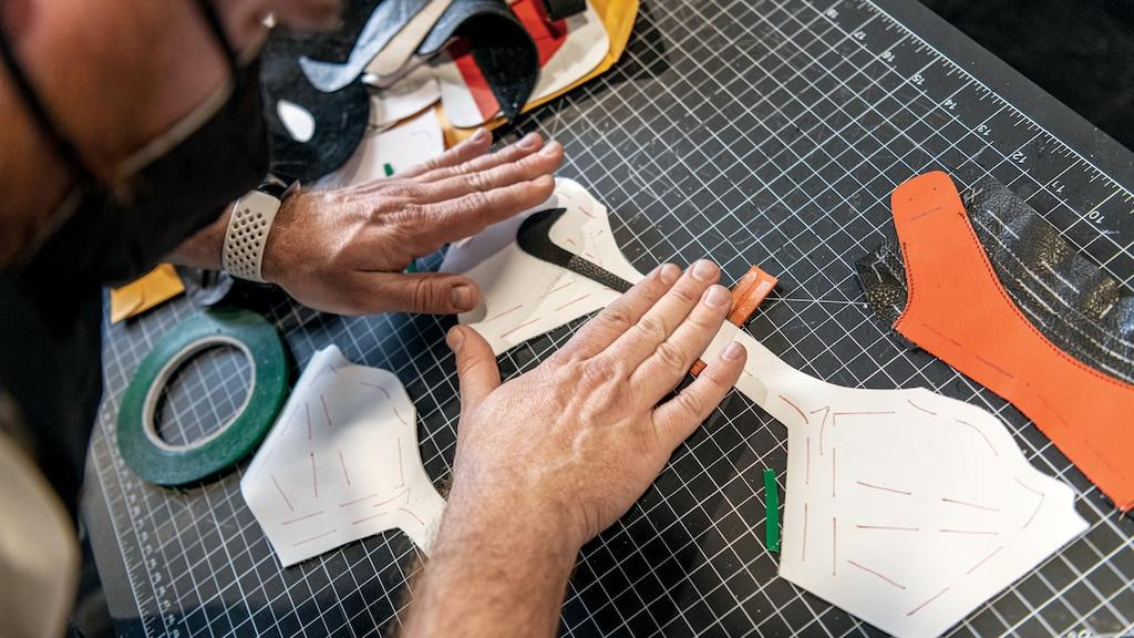 Manos que colocan el logotipo de Nike sobre una pieza blanca en una tabla para cortar tela.