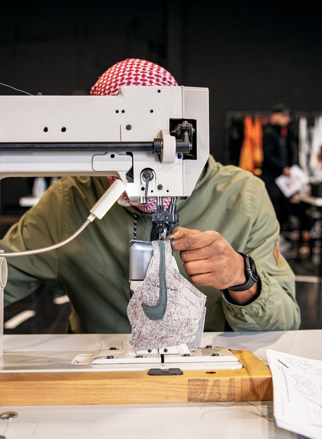Una persona usando una bandana a cuadros rojos y blancos y una camisa verde trabaja en una máquina de coser industrial, su rostro queda oculto tras la máquina. En la máquina hay una pieza de tela blanca con un logotipo de Nike verde.
