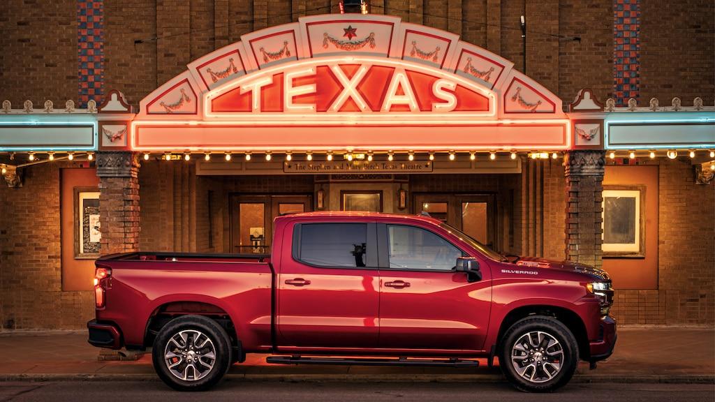 Una camionetaSilverado RSTdiesel roja frente a la marquesina iluminada del teatro Texas en Seguin.