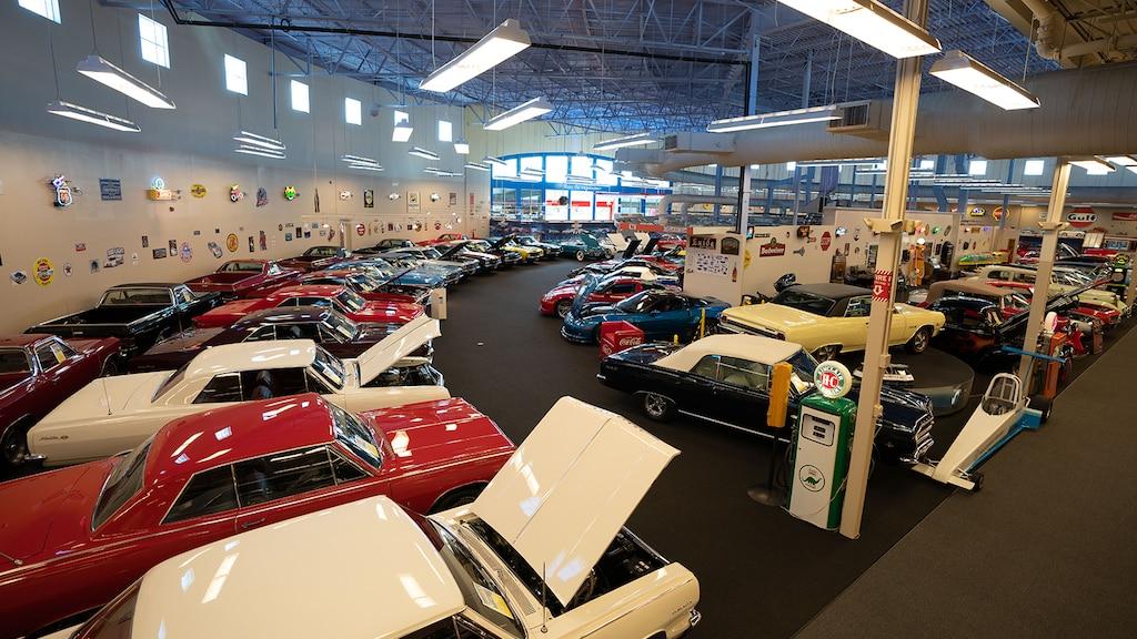 Una colección de vehículos adentro de Muscle Car City, que incluye un Impala antiguo y un Corvette contemporáneo.