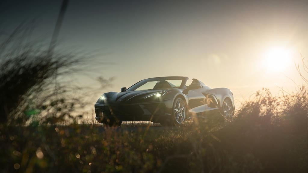 Silueta de un Corvette Convertible 2020 enBronce Zeus Metálico en contraste con el sol poniente en un camino de la costa en Carolina del Sur.