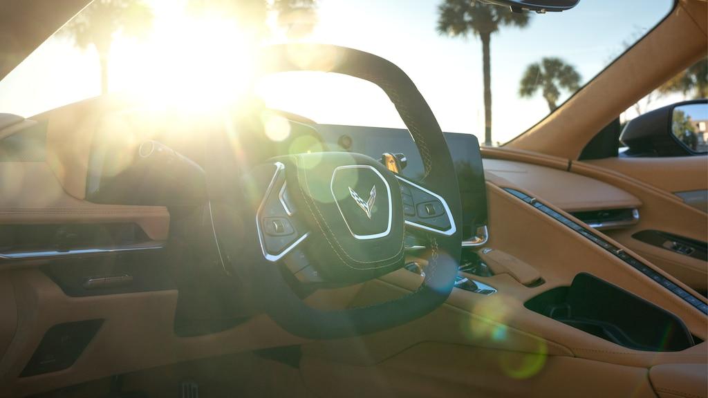 El interior forrado en piel Napa y volante deportivo de un Corvette Convertible 2020; a través del parabrisas se ven unas palmeras y el brillo del sol.