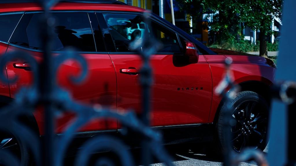 Vista de una Chevy Blazer roja a través de una puerta de hierro forjado.