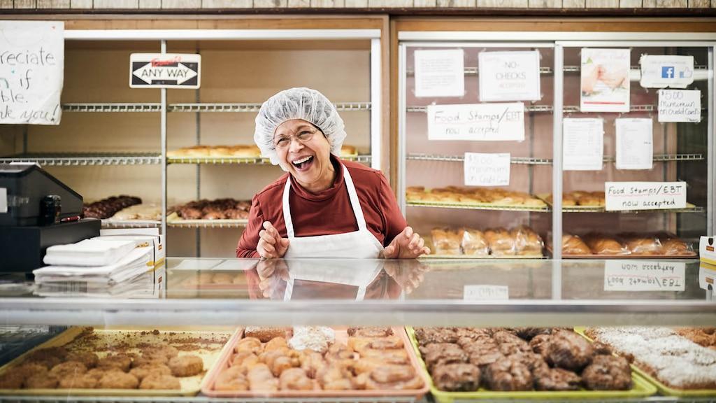 Vera Slamka de pie detrás de un mostrador de vidrio con masas, sonriente y con un delantal y una redecilla en la cabeza.