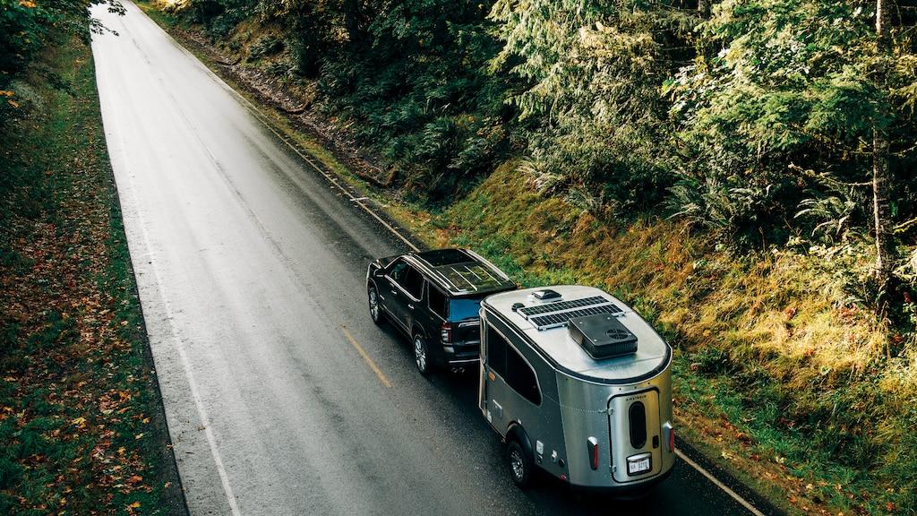 Una Chevy Tahoe negra con un remolqueAirstream Basecamp X vista desde arriba andando cuesta abajo por uncamino de alquitrán en un bosque.