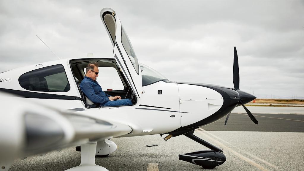 Un hombre en la cabina de un pequeño avión, visto desde afuera.