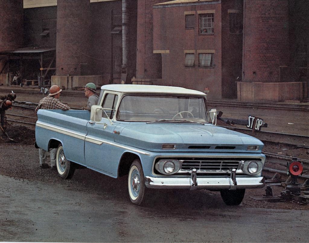 Una fotografía vieja del folleto de la camioneta serie C/K 1962 mostrando una pickup azul claro de la serie C/K con dos hombres de pie detrás de la caja.