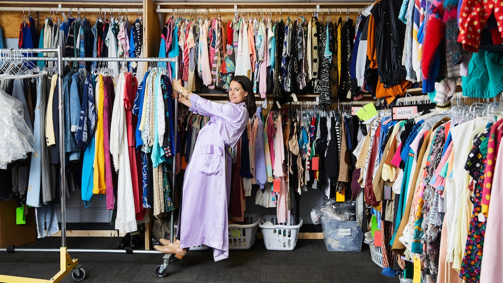 Beth Morgan parada sobre un rack de ropa portátil lleno de vestuarios frente a una pared de racks llenos de principio a fin de vestuarios.