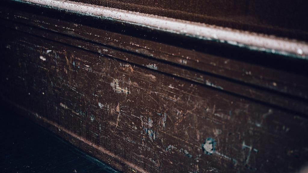 Primer plano del panel de una puerta, que presenta rayones y desgaste, de una vieja camioneta Chevy.