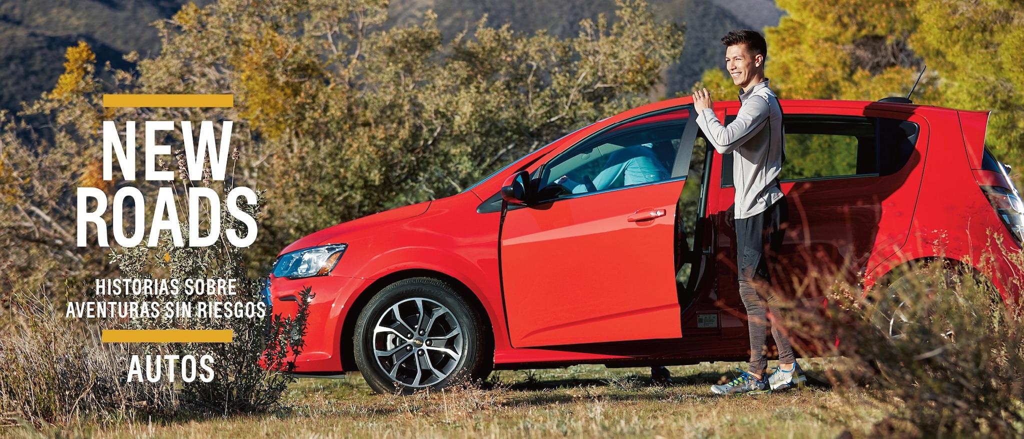 Un hombre con ropa deportiva se encuentra afuera de la puerta del copiloto de un hatchback Chevrolet Sonic.