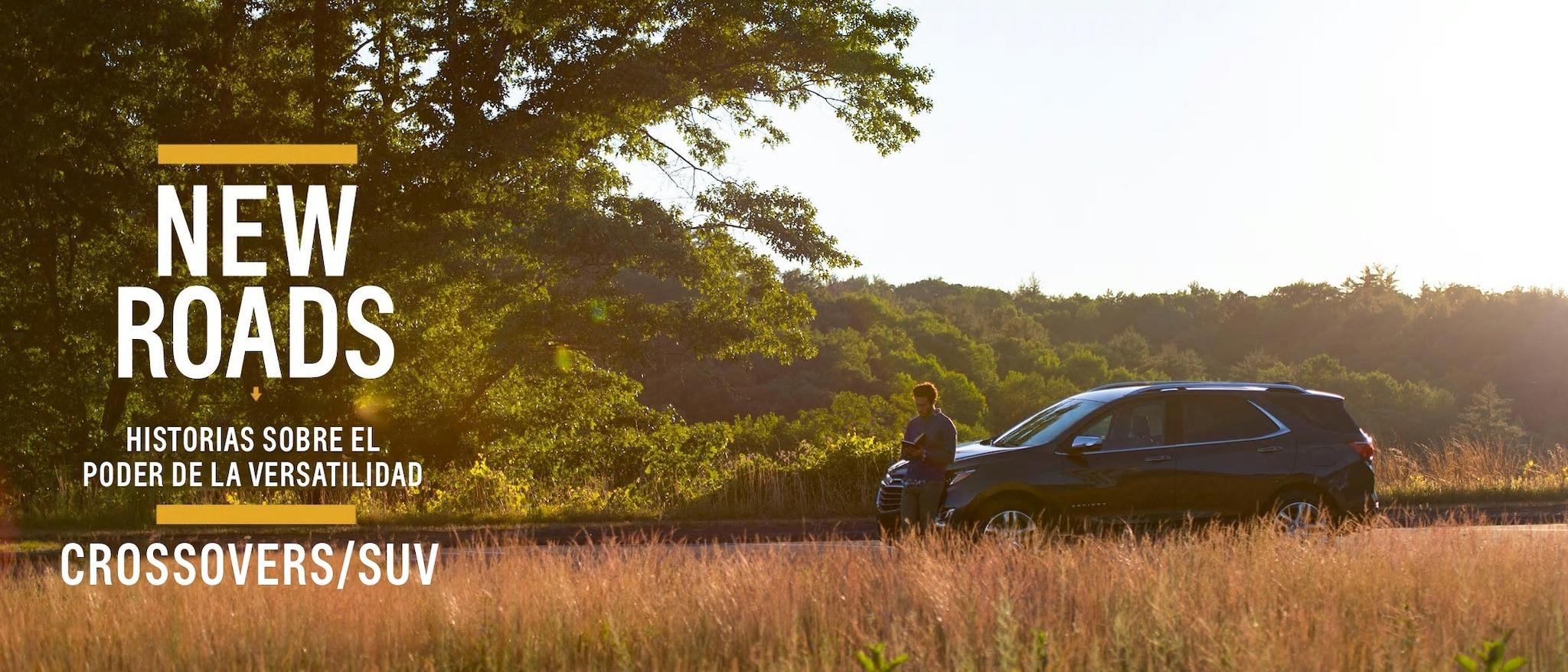 Un hombre se encuentra en frente de una Chevrolet Equinox estacionada al costado del camino cerca de un campo dorado.