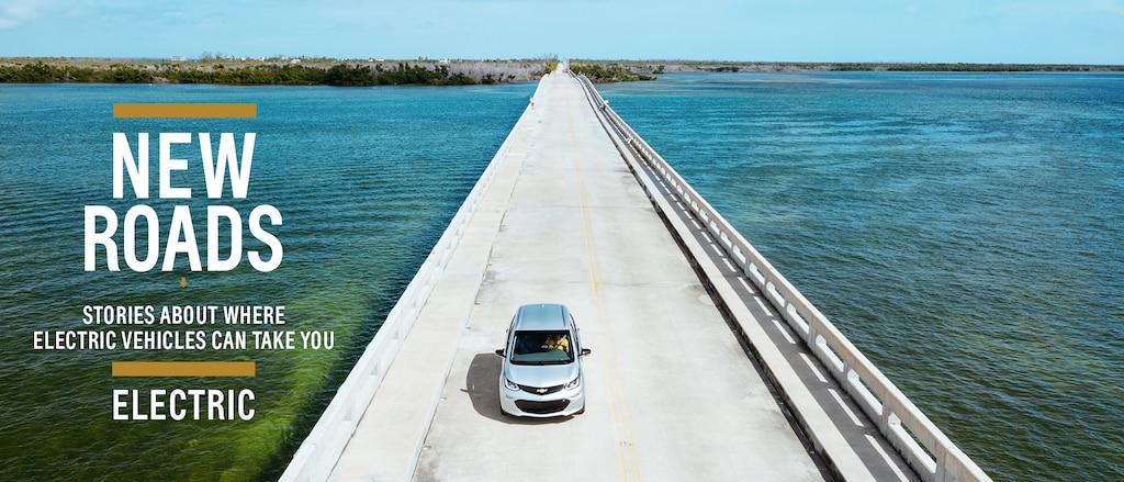 Un Chevrolet EV blanco transitando un camino rodeado de árboles.