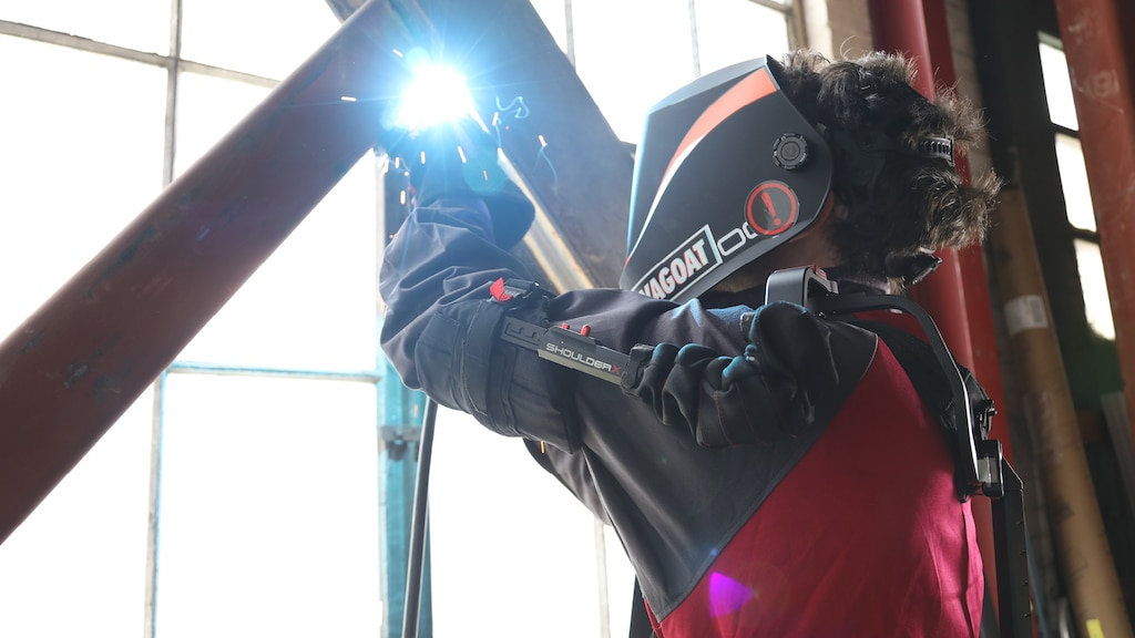 A person wearing a high-tech exoskeleton suit and a face shield welds two iron bars that cross in front of a large warehouse-type window.