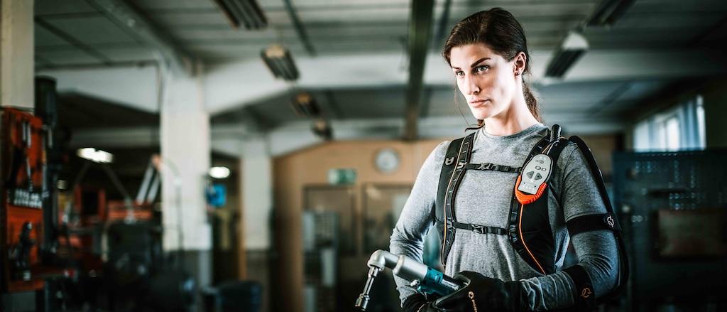 Una mujer usando guantes y exoesqueleto de alta tecnología para aumentar su fuerza, de pie en una planta industrial con una llave de impacto en la mano.