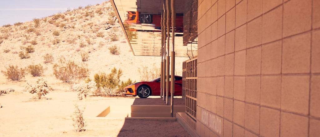 UnCorvette 2020 enRojo Antorcha estacionado a la sombra junto a una casa contemporánea en el Sudoeste desértico, con un paisaje desértico soleado de fondo.