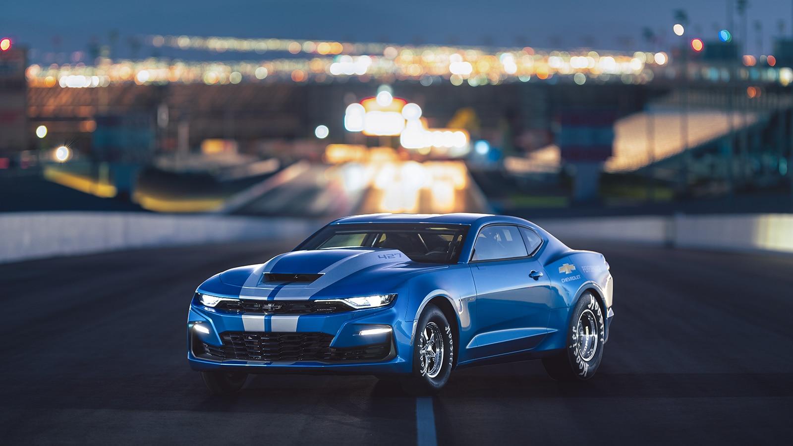 Visto desde arriba, un eCOPO Camaro Concept de carrera de dragsters eléctrico acelera sus neumáticos en la pista.