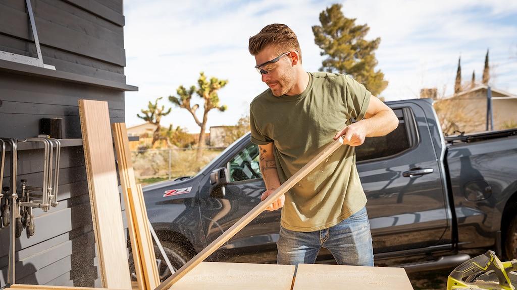 Un hombre usando ropa de trabajo y gafas de seguridad mueve madera frente a una camioneta pickup Chevy Silverado de color negro.