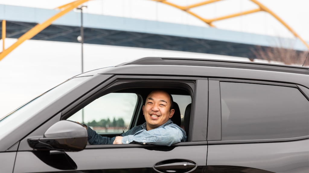 Erik Kennedy sonríe mirando a la cámara desde la ventanilla abierta del lado del conductor de su Trailblazer RS 2021 negra, estacionada debajo de un puente azul con arcos de soporte amarillos.