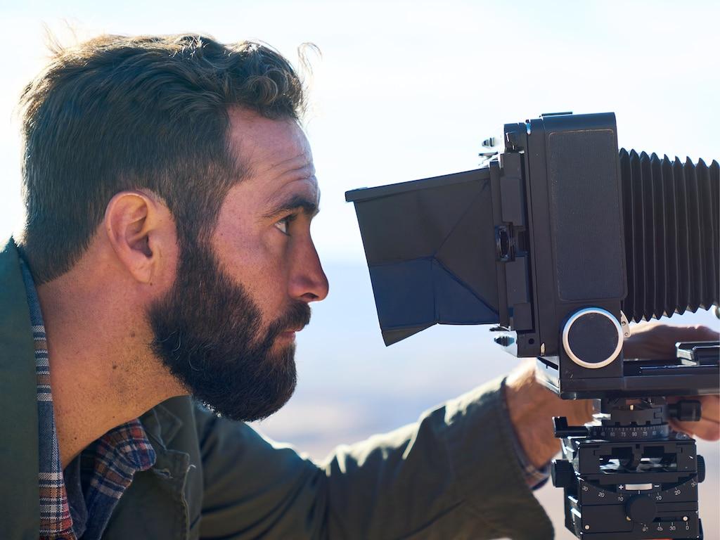 Un hombre con barba mira a través del lente de una cámara de gran formato en frente de un fondo fuera de foco del desierto alto de Arizona.