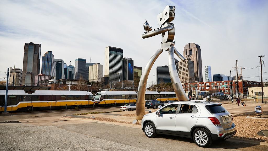 Una Chevrolet Trax color plata en la calle al lado de una escultura moderna con el horizonte de Dallas en el fondo.