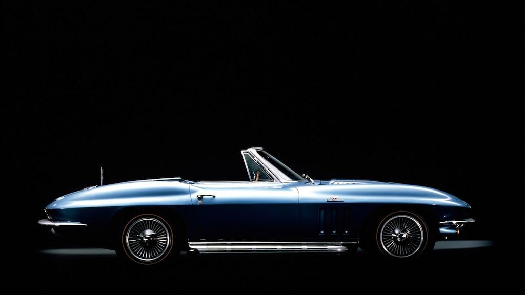 Un Corvette convertible de 2.ª generación (C2, 1963-1967) en Azul con la capota baja visto desde un costado contra un fondo negro.