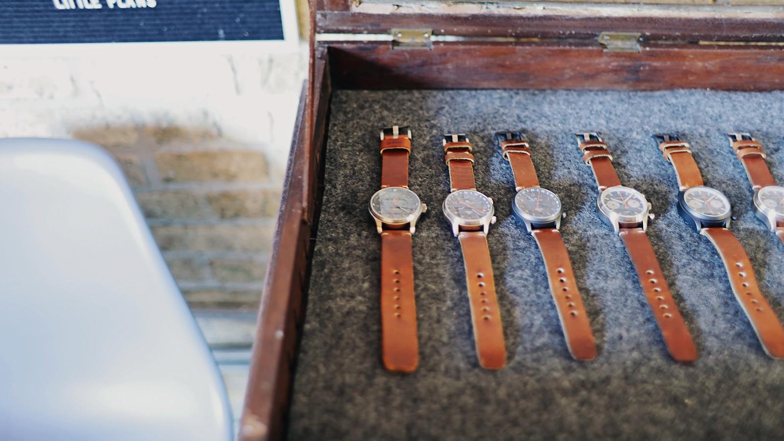 Una hilera de relojes con correas de piel marrón en una caja de madera con forro de felpa.
