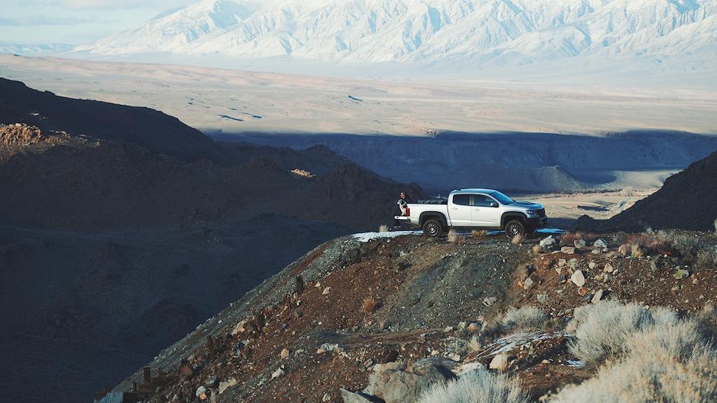 Una camioneta pickup Chevy Colorado ZR2 Bison de color plata está detenida en una cornisa elevada sobre una colina en las montañas de California, con el desierto y las montañas en el fondo.
