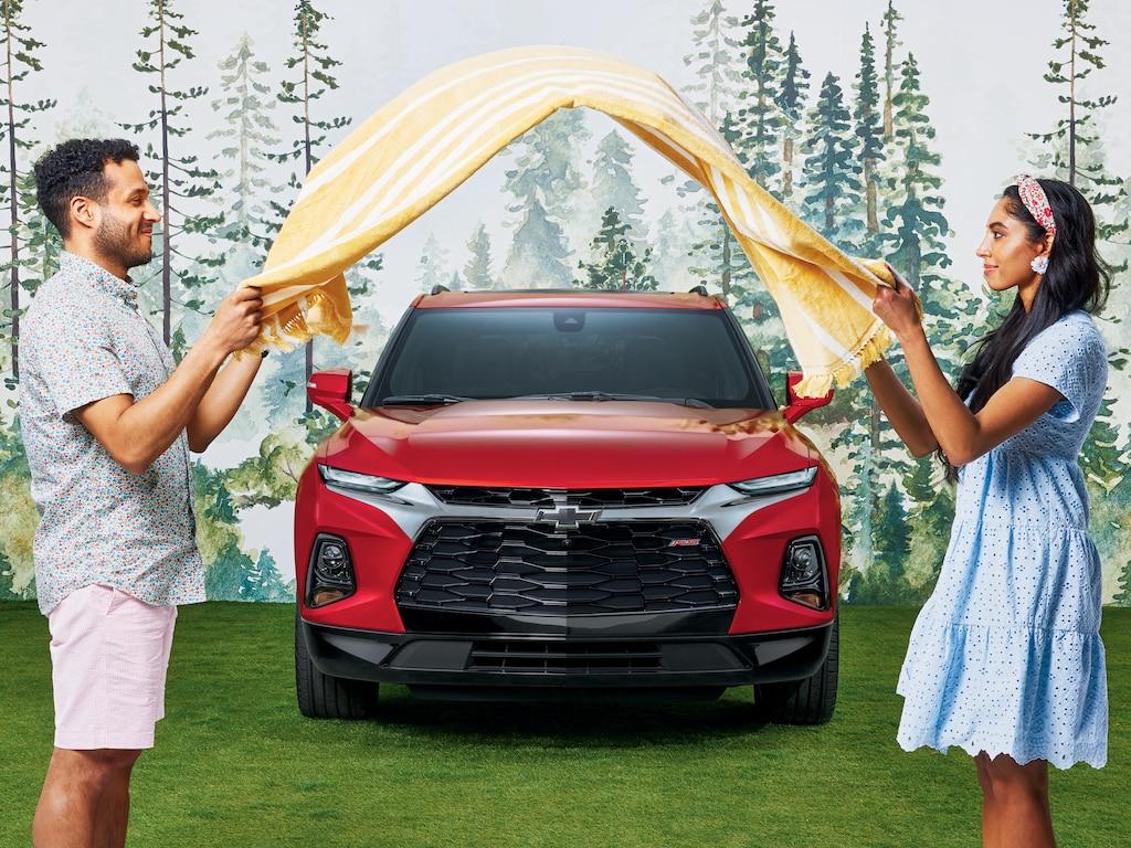 Dos personas frente a frente adelante de una Chevy Blazer RS en Rojo Cereza Tintcoat agitando una manta de pícnic con rayas amarillas.