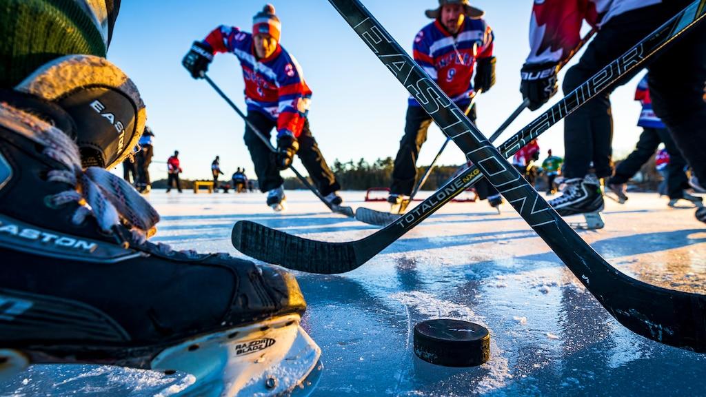 Un grupo de jugadores de hockey sobre un estanque congelado se disputan el disco, vistos desde el nivel del hielo justo detrás de uno de los jugadores.