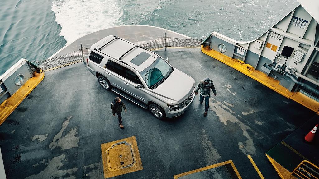 Padre e hijo caminan pasando una SUV Chevy Tahoe en la cubierta de un transbordador que está en marcha.