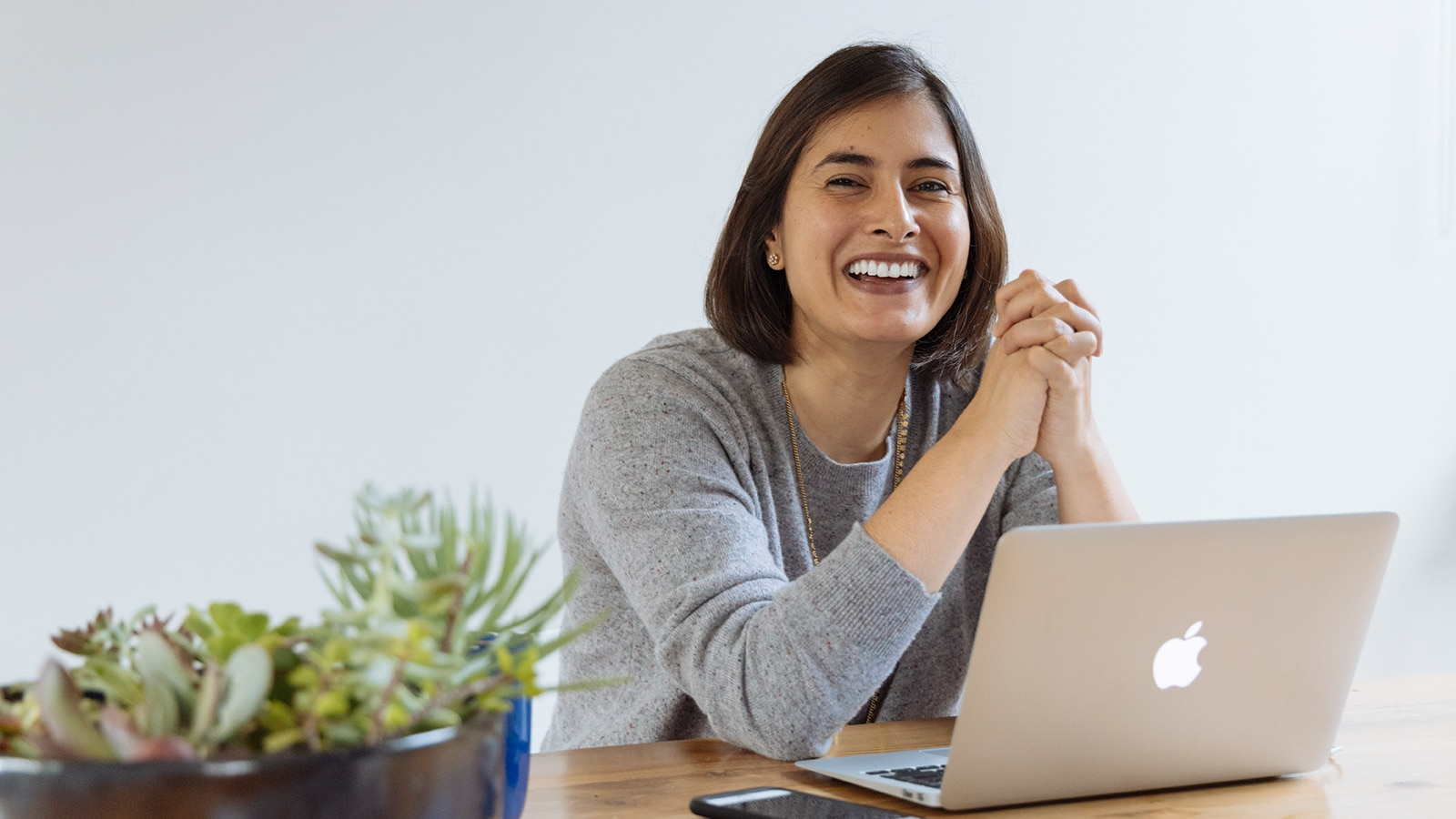 A woman sits at a table smiling with an open laptop and cellphone infront of her.