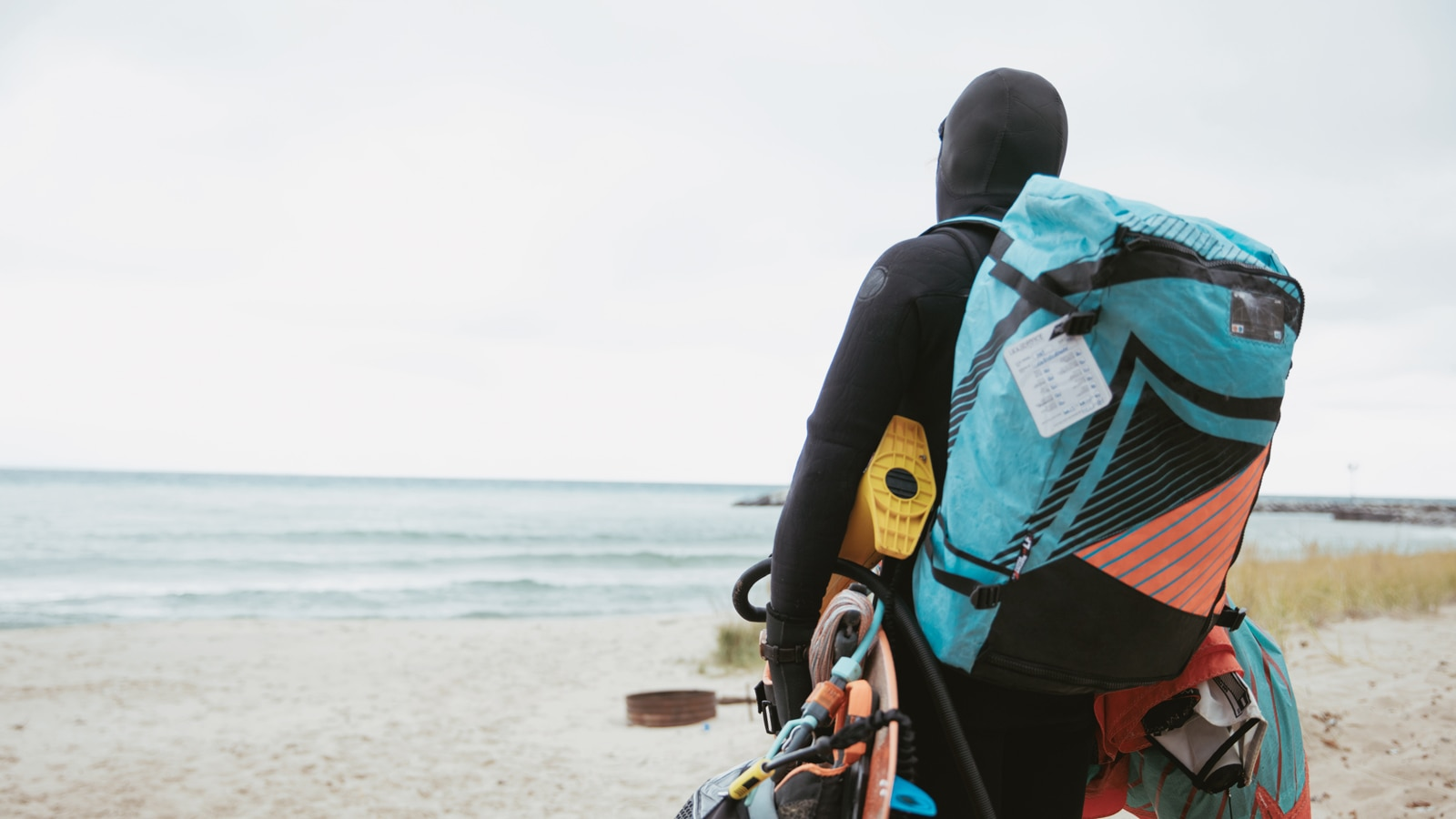 Persona con traje de neopreno caminandopor la playa hacia el Lago Michigan con la mochila repleta y transportando su equipaje.