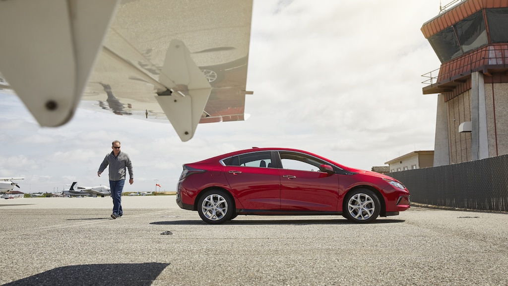 El emprendedor Eli MurrayMetzger se encuentra al lado de un Chevrolet Volt y un avión.