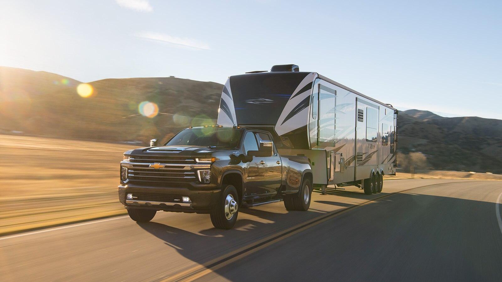 Una camioneta Silverado HD 2020 de color negro transporta un trailer grande por una carretera de dos carriles con colinas en el fondo.