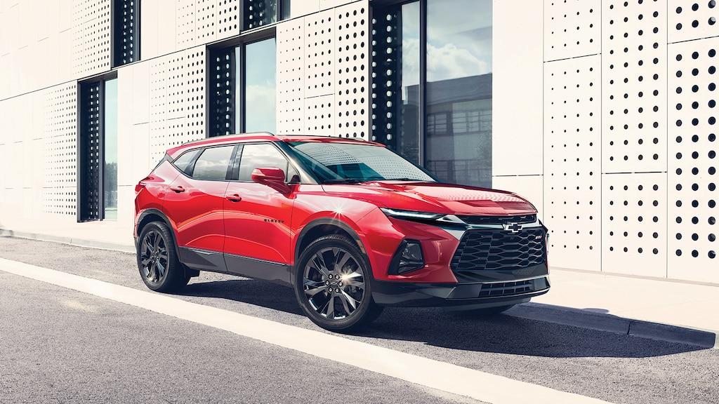 La parte delantera y el lado del acompañante de una SUV Blazer RS en color Rojo estacionada al lado de un edificio de diseño contemporáneo.