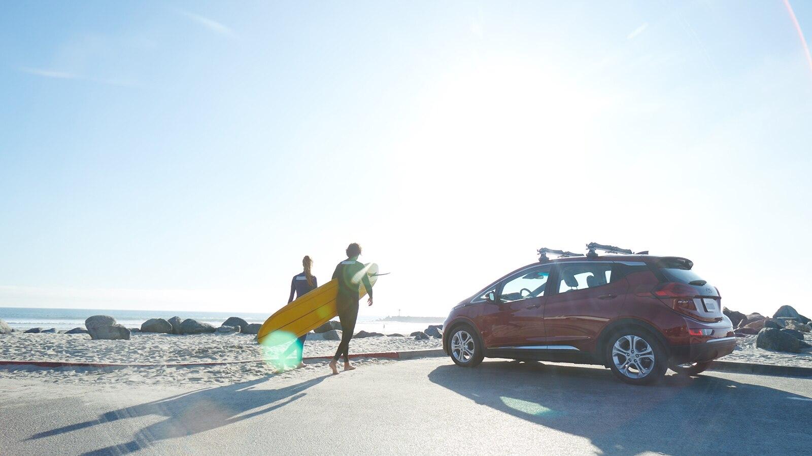 Dos personas en trajes de neopreno caminan desde un estacionamiento hasta la playa llevando una tabla de surf. Un Chevrolet Bolt EV color rojo detenido en un estacionamiento.