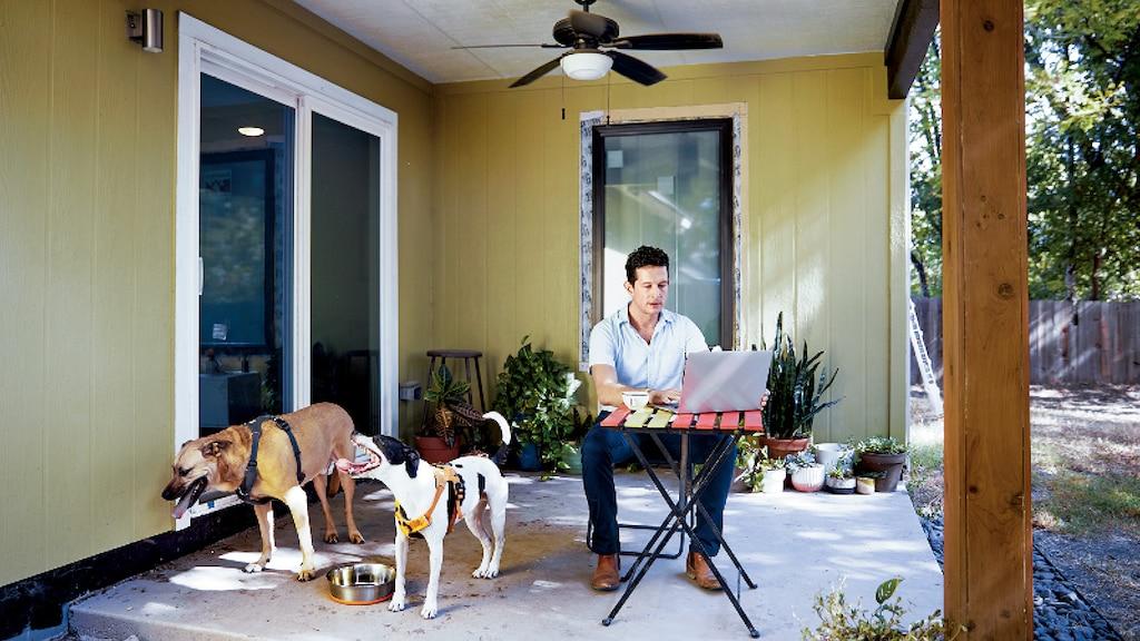 El arquitecto Jon Hagar usa una laptop sentado en una mesa que se encuentra en un patio cubierto y sus dos perros están sentados a su lado.