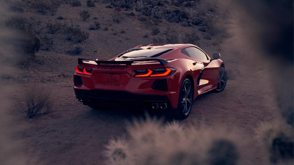 Un coupe Corvette 2020 en Rojo Antorcha en un paisaje desértico al atardecer, visto desde atrás con las luces de freno encendidas.