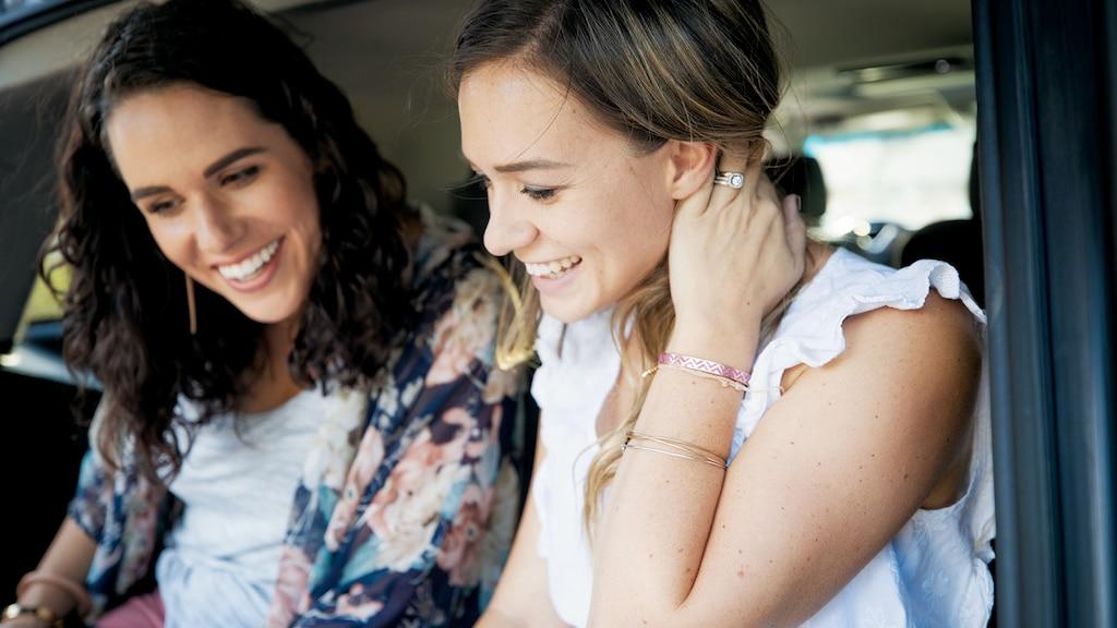Primer plano de Courtney y Brittany McLachlan mirando algo sentadas en la Chevrolet Tahoe de Brittany.