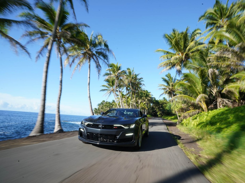 A 2020 Camaro SS is seen from the front on a flat paved road lined with palm trees next to the ocean.