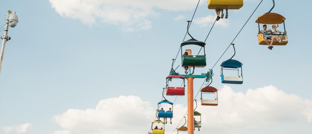 Asistentes a la feria estatal paseando en coloridas góndolas.