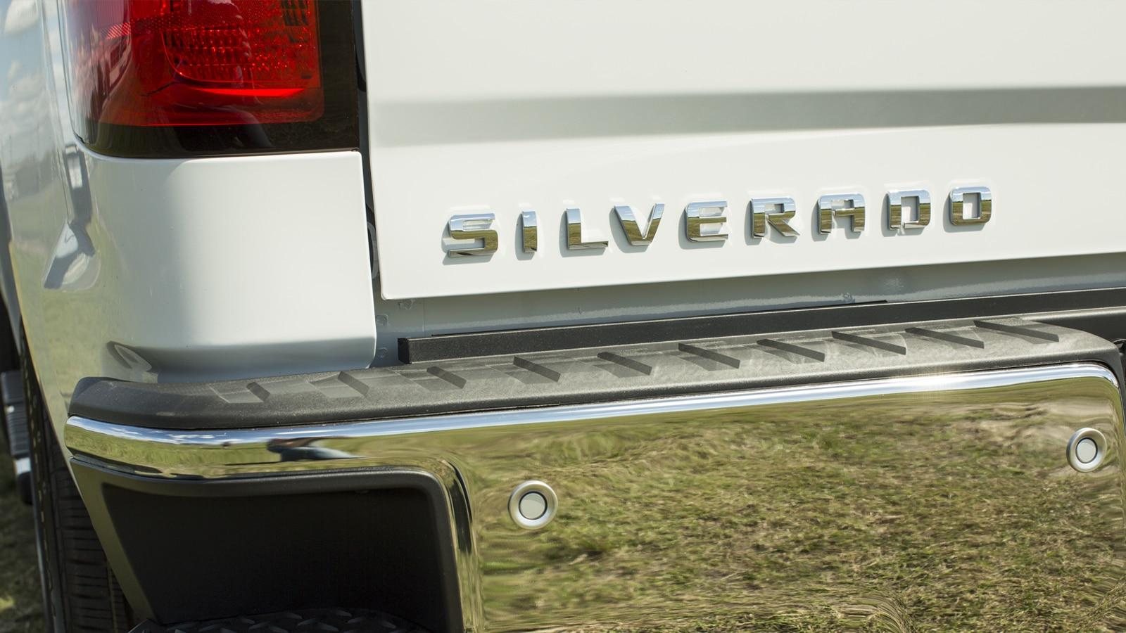 Primer plano del emblema de la Silverado sobre la puerta trasera de una camioneta blanca.