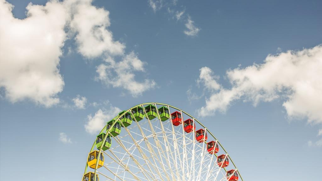 La parte de arriba de una vuelta al mundo se destaca al frente de un cielo azul con nubes.