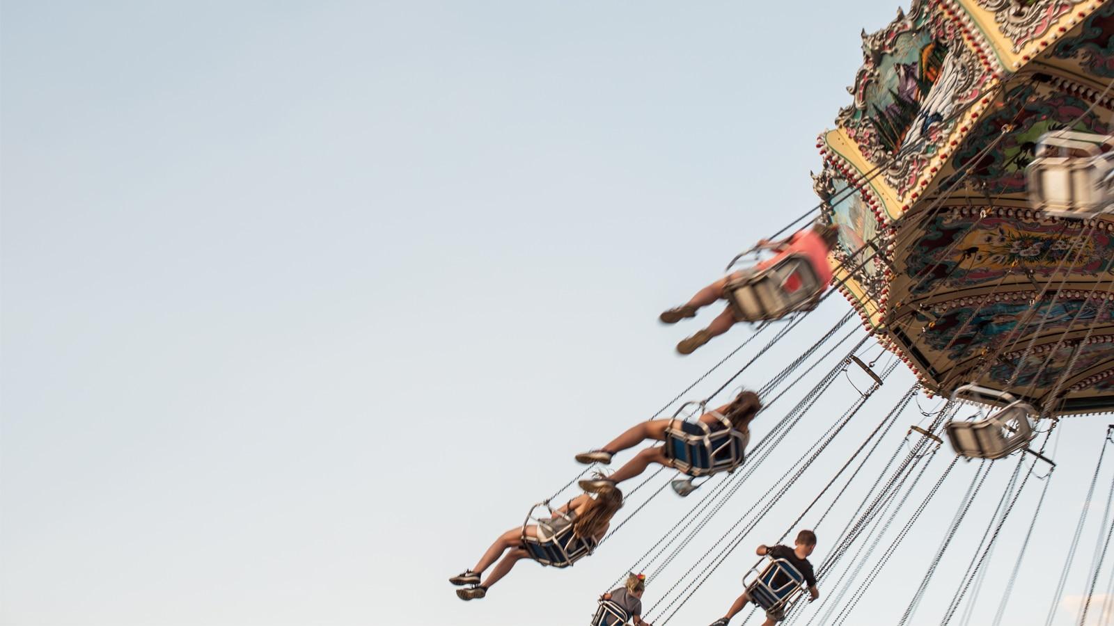 Asistentes a la feria estatal disfrutan de balancearse por el cielo de verano.