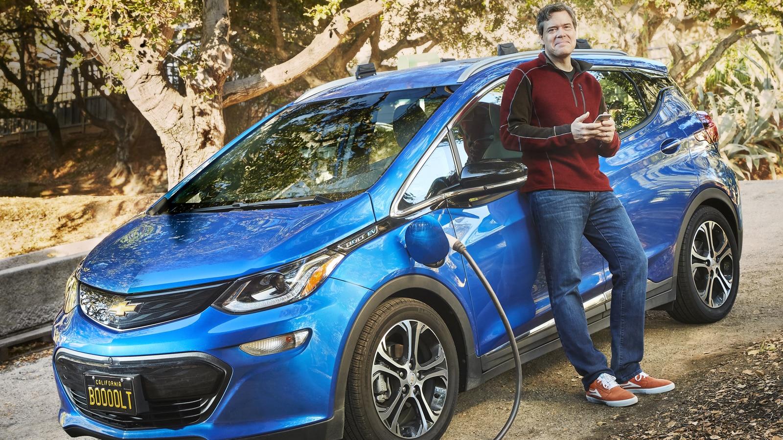 Ethan Stock parado al lado de su Chevy Bolt EV 2017 color Azul, que está enchufado para cargarse.