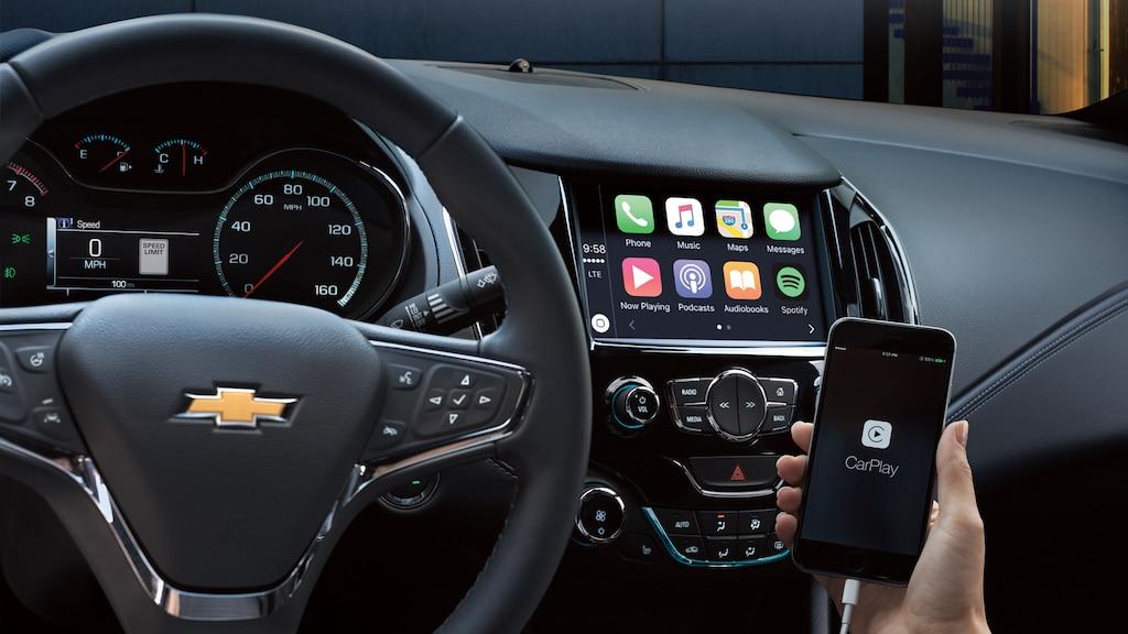 Una mano sosteniendo un teléfono con la interfaz Apple CarPlay abierta.