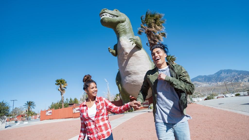 Una pareja tomada de las manos frente a uno de los Cabazon Dinosaurs.