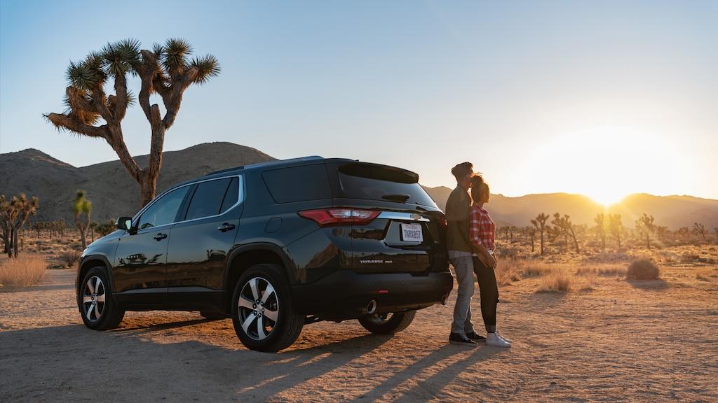 Una pareja de pie detrás de la Chevrolet Traverse mientras se pone el sol.