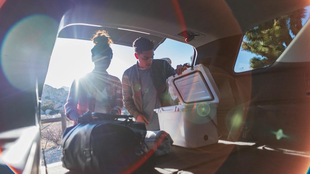 Una pareja revisando los equipos en la amplia área de carga de la Chevrolet Traverse.