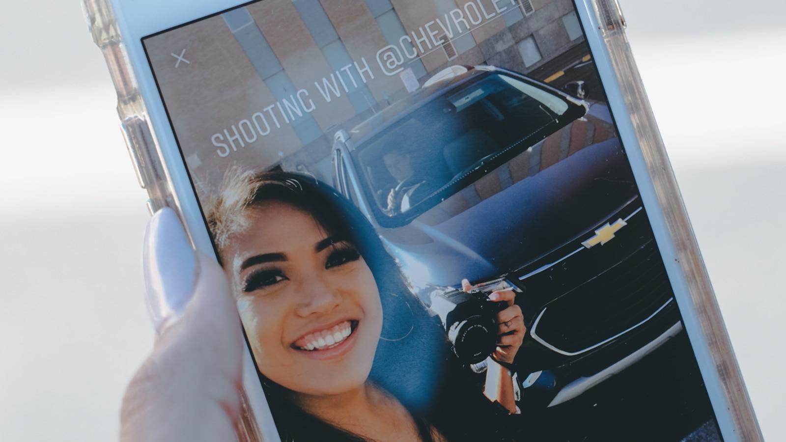 La pantalla del teléfono de Mo Calderon muestra un autorretrato frente a la Chevrolet Trax.